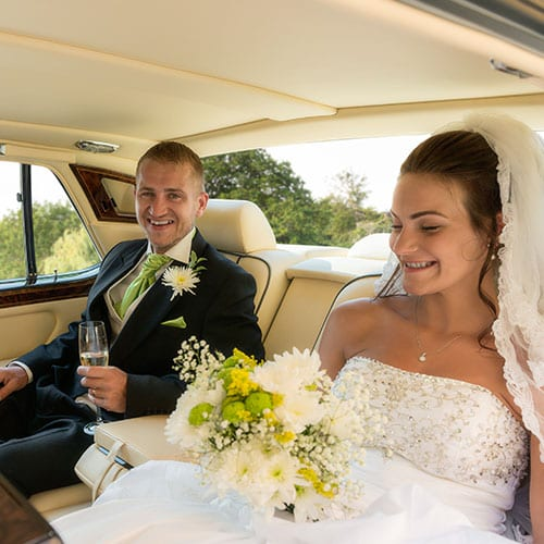 bride and groom in back of Bentley Brooklands with champagne