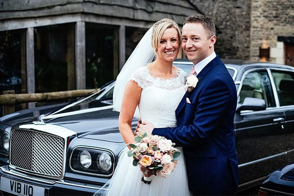 bride and groom standing in front of Bentley Arnage on their wedding day