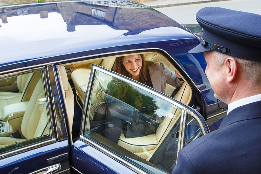 client getting out of Bentley Brooklands with chauffeur holding door open