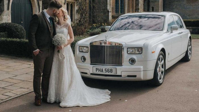 Bride and Groom kissing in front of the Rolls-Royce Phantom Wedding Car