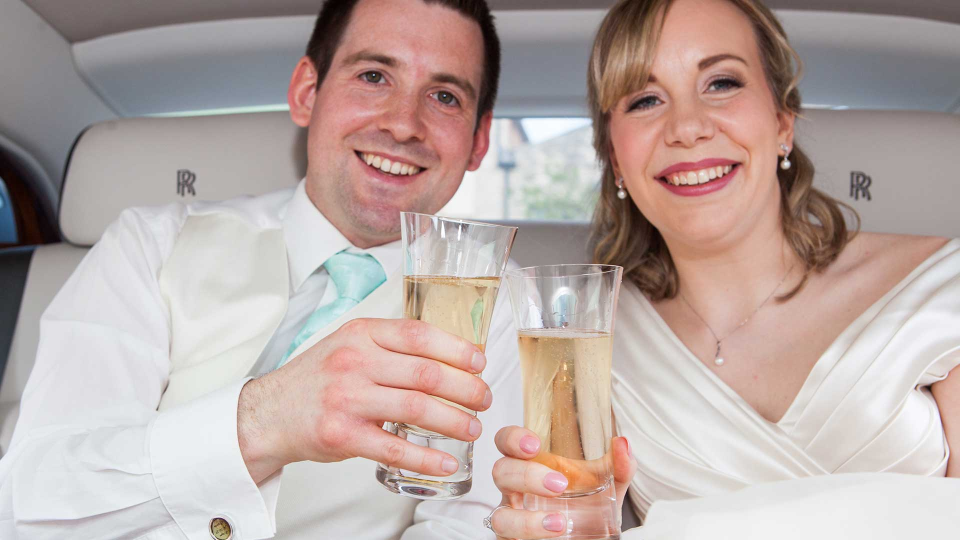 Newly-wed couple Mr and Mrs Bracher enjoying a celebratory glass of Champagne in the Rolls-Royce Phantom