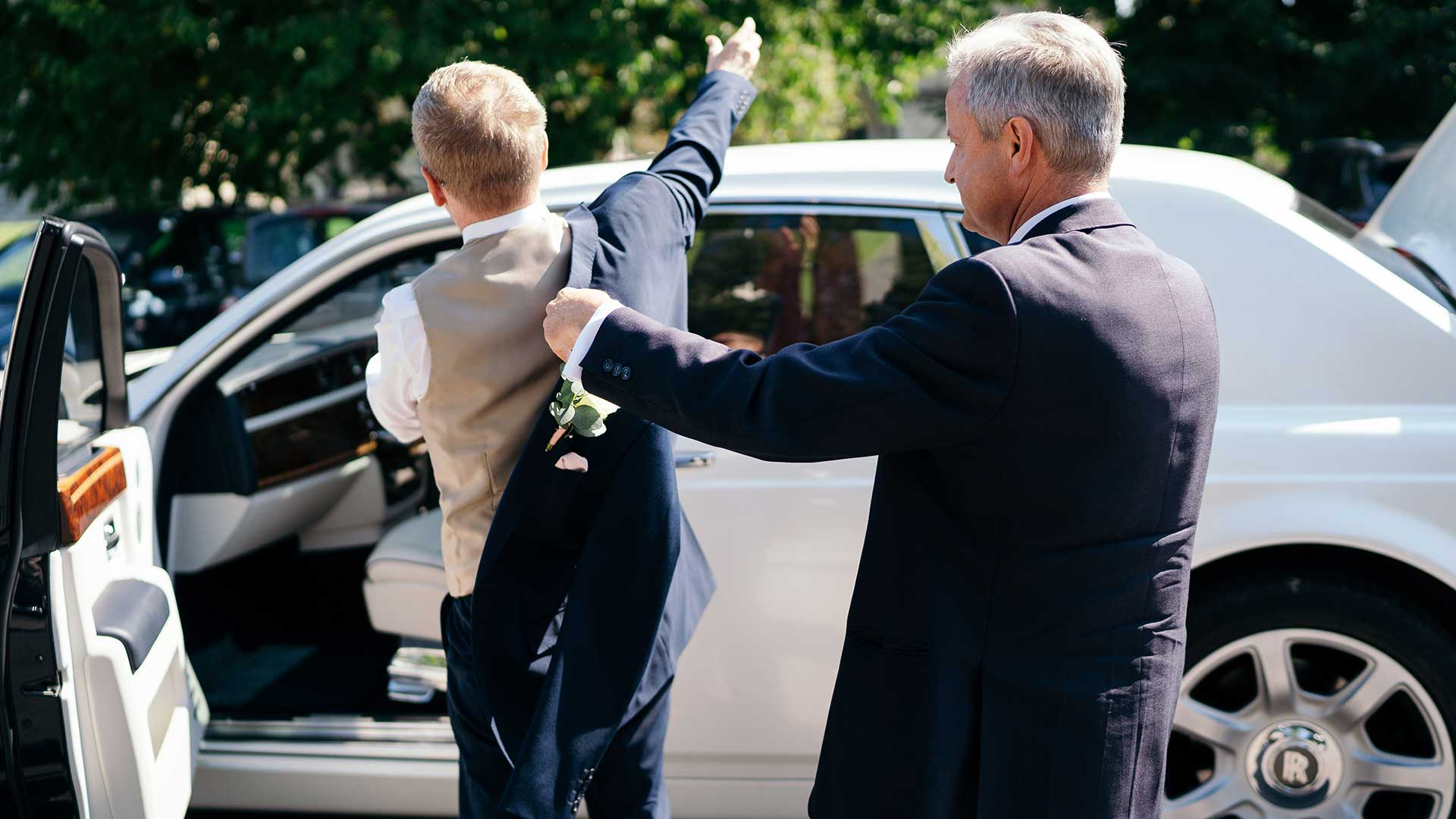 Chauffeur and owner of Azure Wedding Cars, David, assisting with putting a jacket on